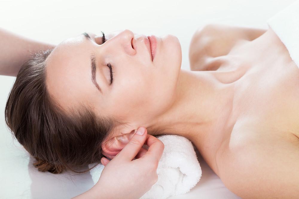 Auricular reflexology, woman having ear reflexology
