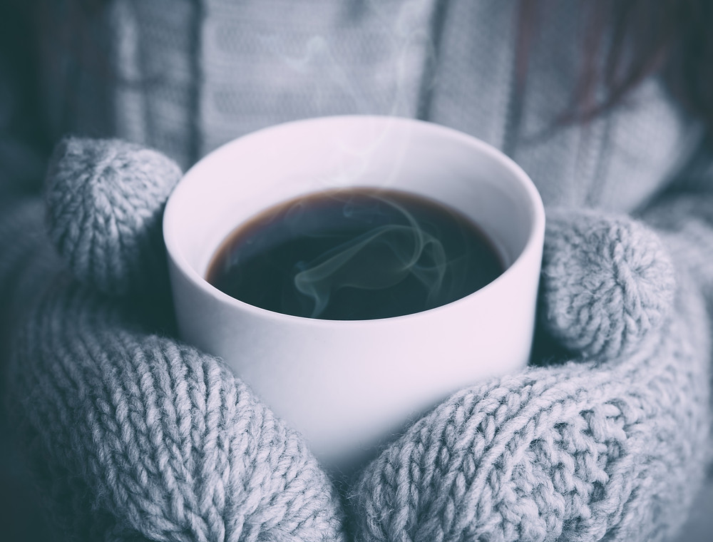 Hot drink in a mug held by hands in mittens