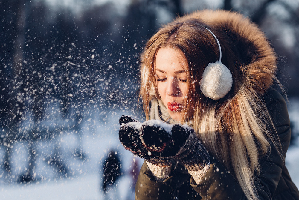 Woman blowing snowflakes from gloves