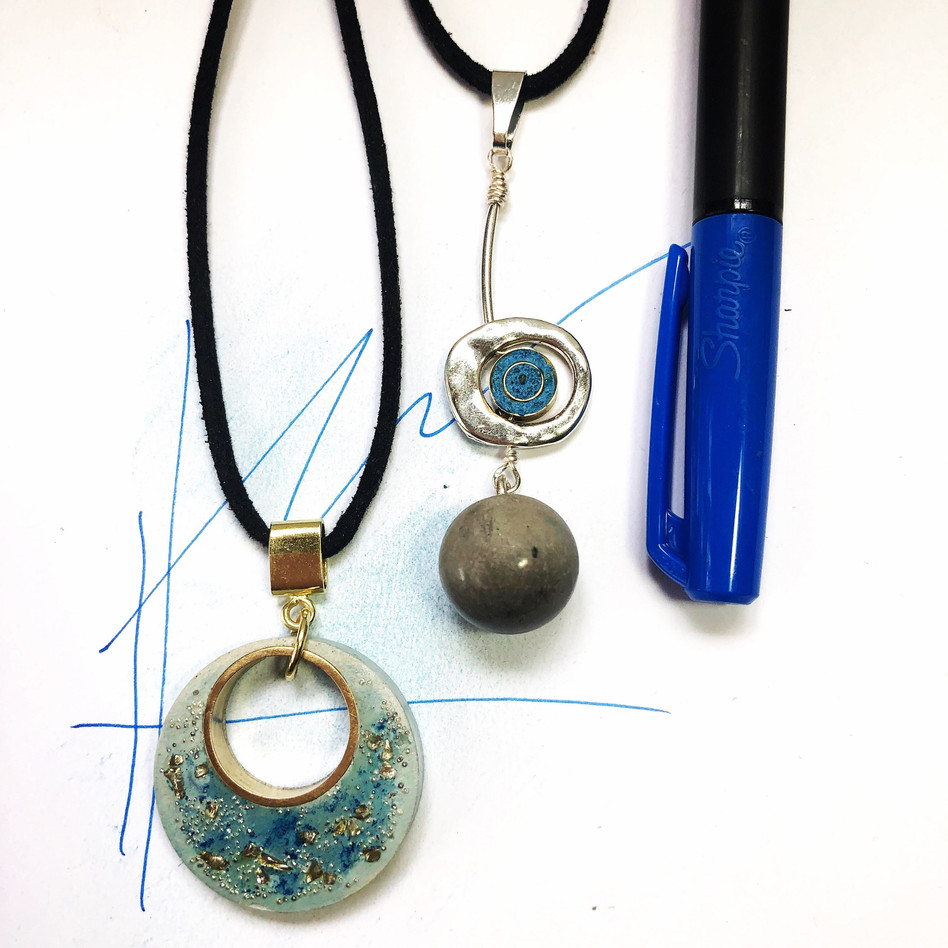 "• (R) Circle Concrete Necklace with Blue and Gold Flakes. Size:  1 1/8""  Materiales: Concrete circle, brass ring, glod plated bail and 16"" plus 2"" extension black cord.  Code: NC398 $25   •(L) Blue Eye Necklace.  Materiales: Gray concrete bead, brass blue bead, silver plated bead and bail,16"" plus 2"" extension black cord.  Code: NC400 $28"