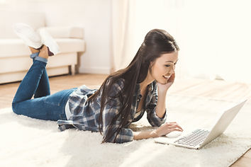 young-woman-lying-on-carpet-and-using-la