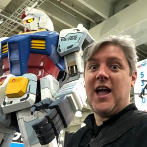 man next to large Gundam statue