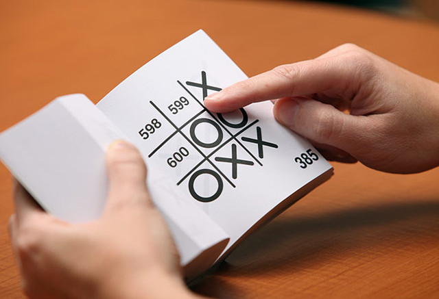 hands holding an open book which shows a tic-tac-toe grid