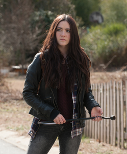 Young woman with long dark hair holding a tire-iron.