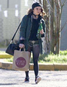 Young woman holding a soda bottle, big purse, and shopping bag.
