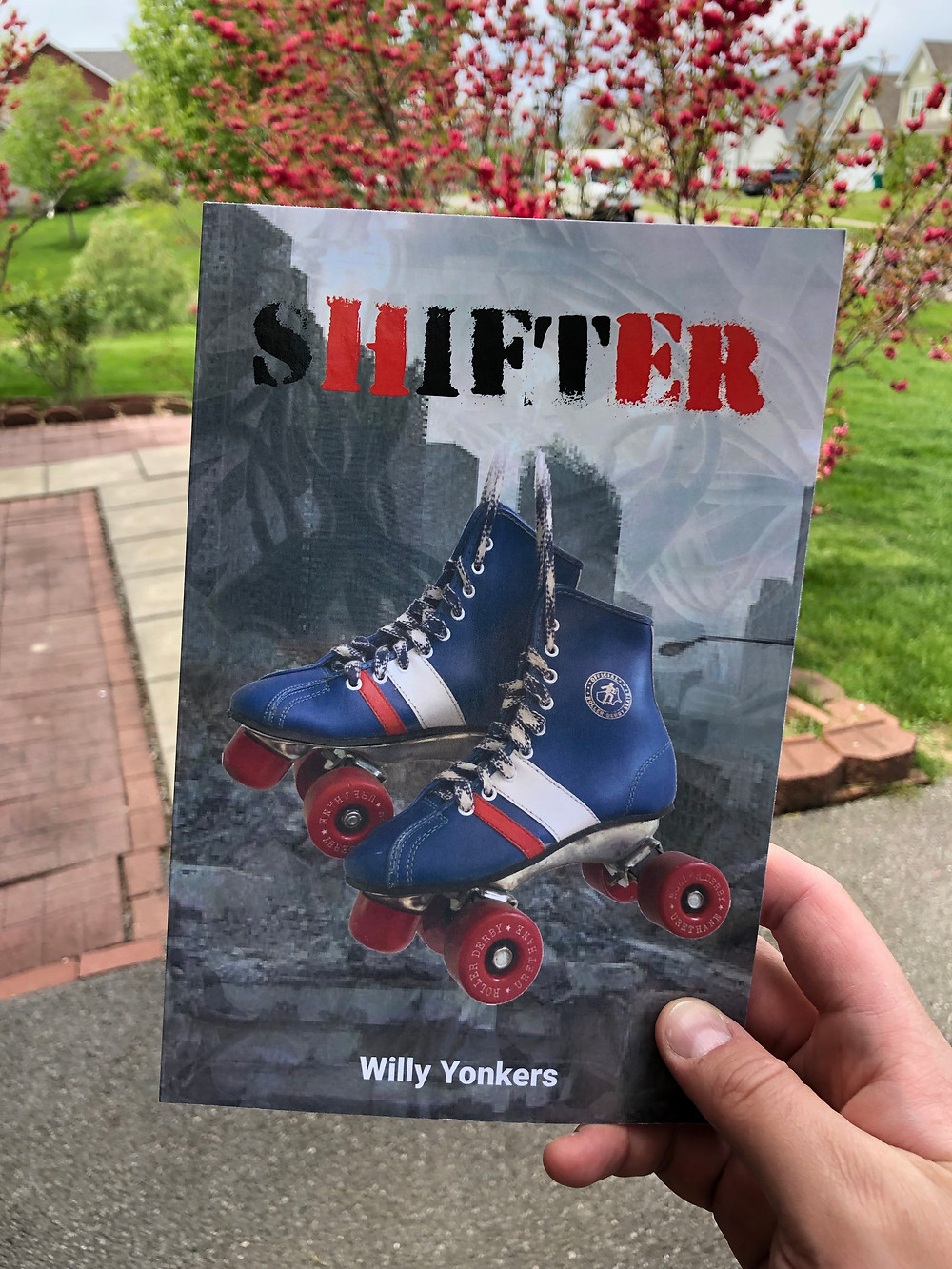 Holding a paperback book with a pair of rollerskates on the cover. Title reads: SHIFTER Author reads: Willy Yonkers.