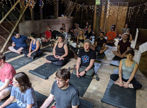 People seated on mats doing yoga in a barn.
