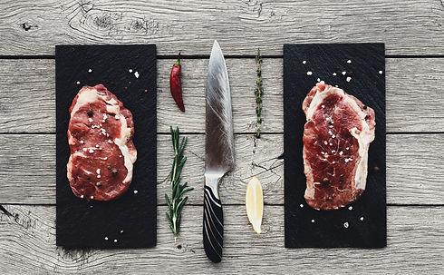 Raw beef steaks on dark wooden table bac