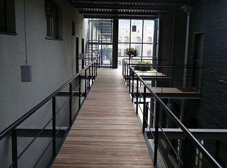 loopbrug op de eerste verdieping bestaande uit een metalen constructie met hardhouten