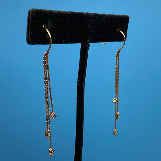Gold pierced earrings with thin chains holding crystals.