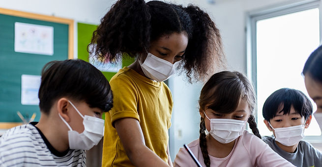A group of Children students wearing medical masks in the classroom. An Asian woman teache