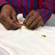 An expert hand working on finishing of kidswear romper