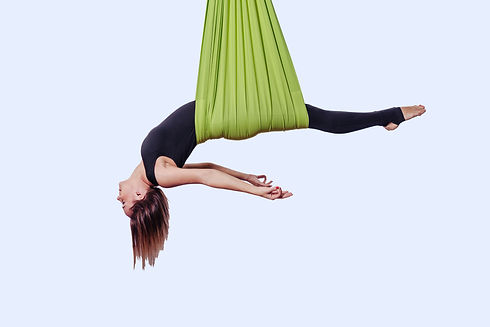 Young woman doing aerial yoga in green h