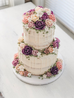 2-tier white chocolate bridal drip cake with buttercream flowers