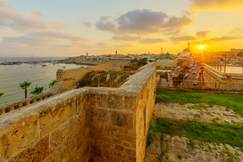 Sunset view with skyline, walls and fishing port, in Acre, Israel