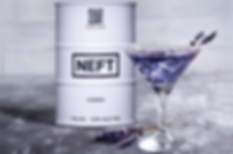 A cocktail glass with a purple drink and sprigs of lavender sitting by a white barrel of NEFT vodka