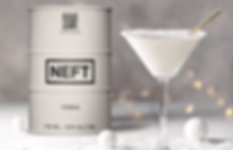 A cocktail glass with a white beverage sitting next to a white barrel of NEFT vodka