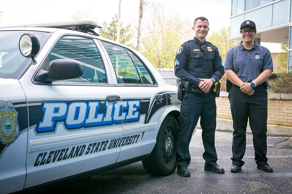 Left to Right: David Thompson and Rachel Lash standing beside a CSU campus police car.