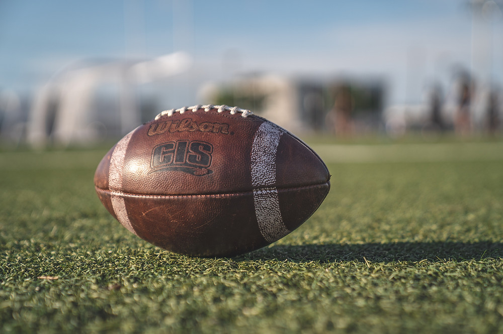 A worn brown football sits on a green field.