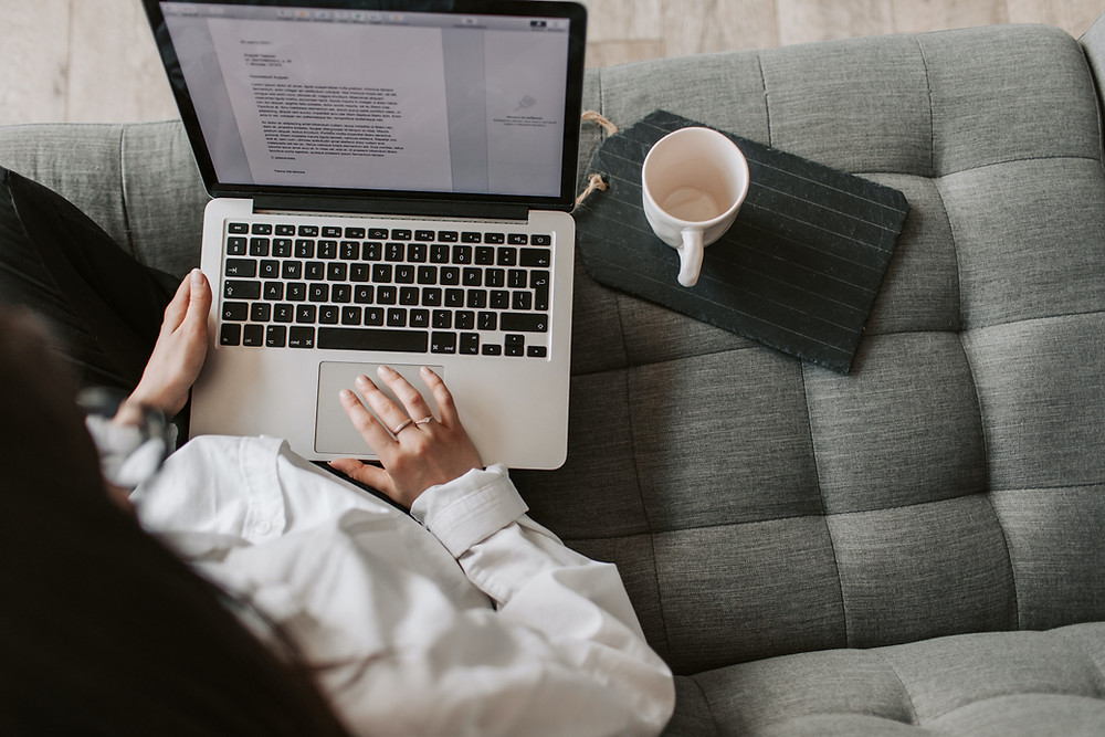 The camera looks down on someone wearing a white button down with an open laptop on their lap and an empty mug to their right. They are seated on a grey tufted couch. There is an open document on the laptop screen.