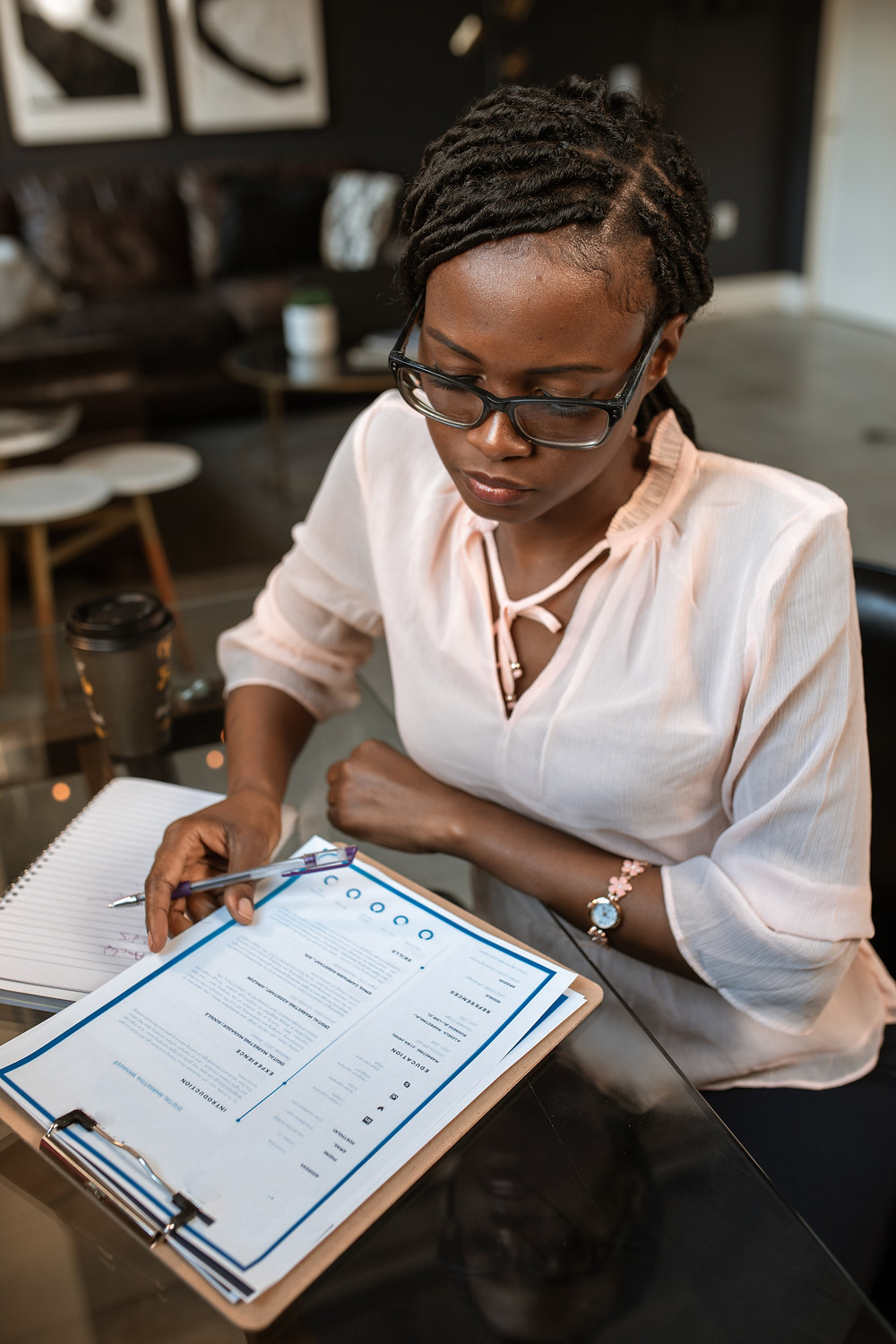 Woman wearing a light pink blouse sits in a cafe looking down at a clipboard with a resume on it. She is holding the clipboard and a pen with her right hand. She is wear glasses and has her hair pulled back into a low ponytail. There are tables, chairs, and wall art behind her.