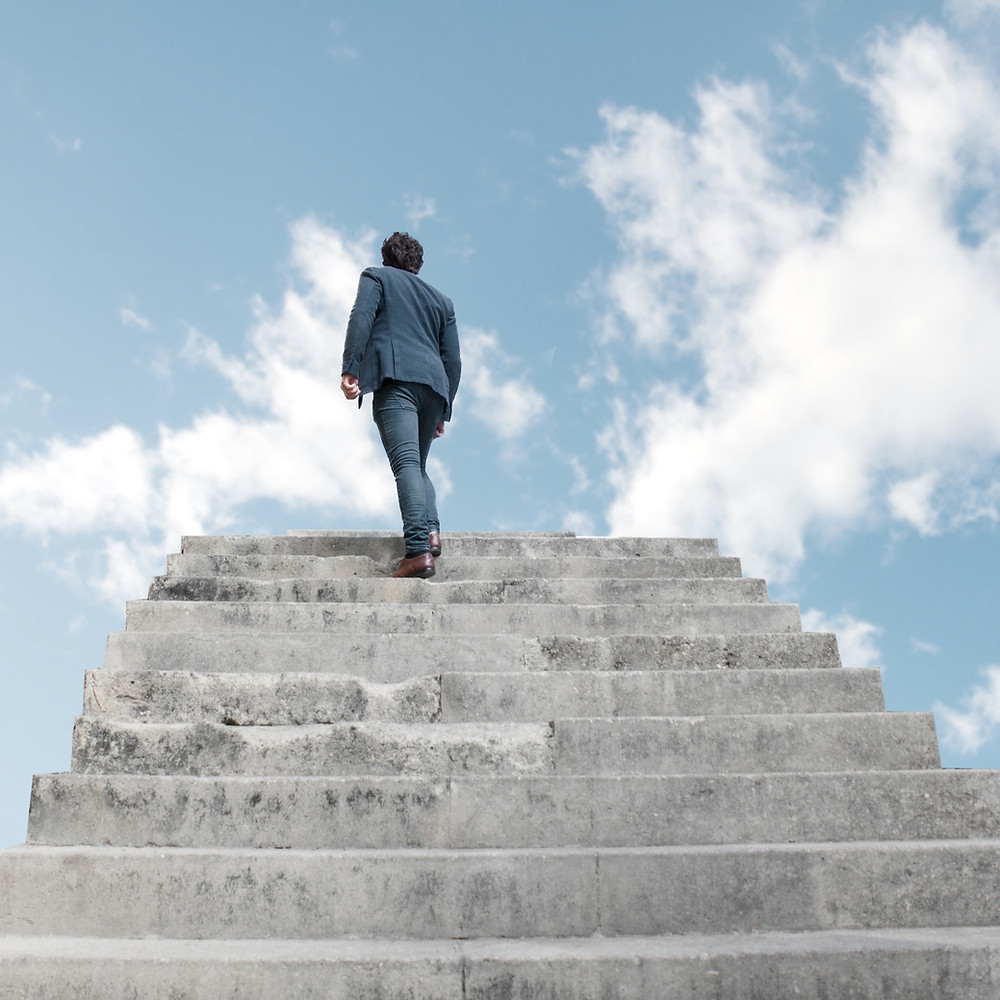 The back of a man in a blue suit and brown shoes, climbing a set of concrete stairs, towards an open blue sky with white clouds.