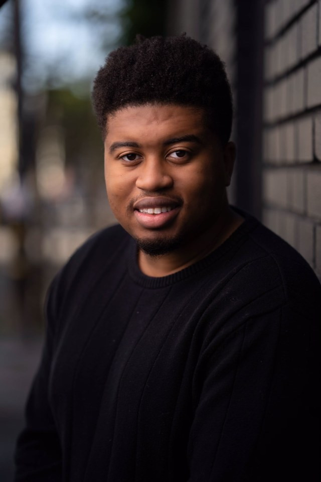 Portrait photo of Dalvin Josias Sejour. He is wearing a black sweater and the photo was taken outside. There is a brick wall behind his left shoulder.