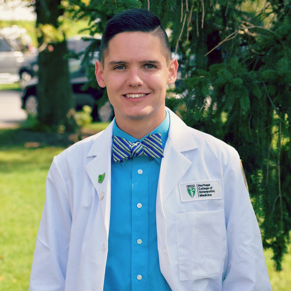 Andrew Dickson wearing a lab coat, blue button down shirt, and striped blue, green, and white bowtie.