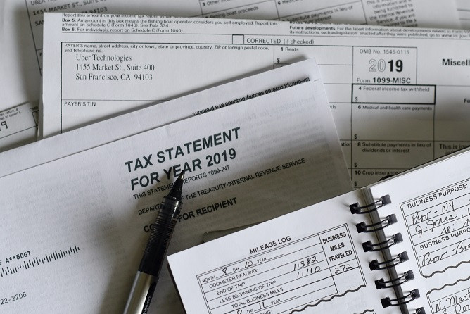 Bird's eye view of: Black and silver pen on white 2019 tax forms. There is also an open spiral bound black and white mileage book.