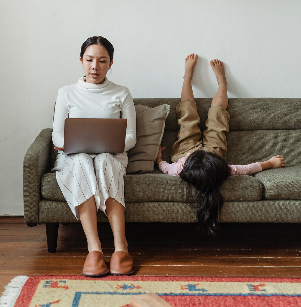 A mother wearing white sits on a brown couch with an open laptop on her lap. Her daughter is to her left, sitting upside down on the couch with her legs against the back and her feet in the air. The floor is brown hardwood with a multi-colored rug on it and the walls of the room are white.
