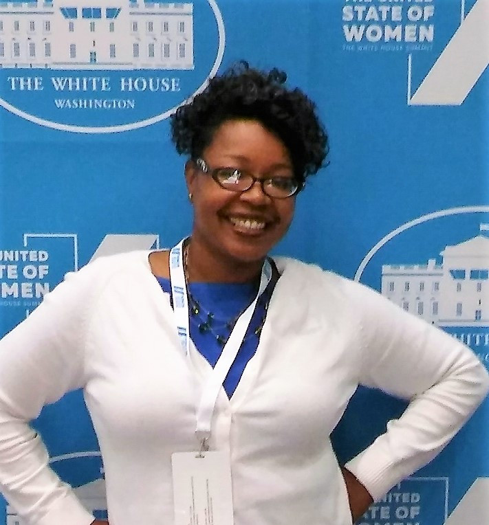 Crystal Franklin standing in front of the White House blue backdrop