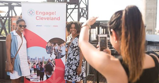 People taking a photo with an Engage! Cleveland sign