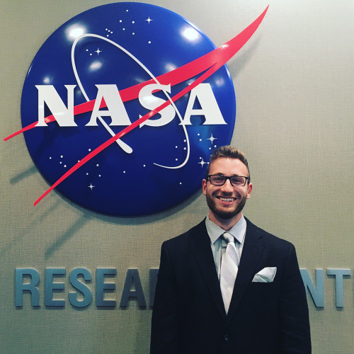 Man standing in front of a NASA sign