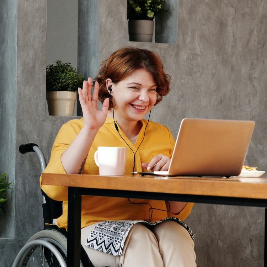 Woman in an orange blouse and tan pants, sitting in a black wheel chair. She is waving to an open laptop, has headphones on, and a coffee cup beside her.