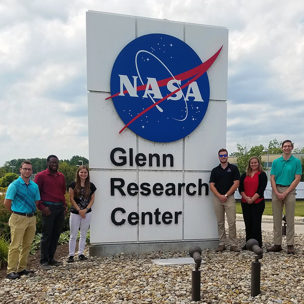 A group of 6 people standing around NASA's Glenn Research Center sign