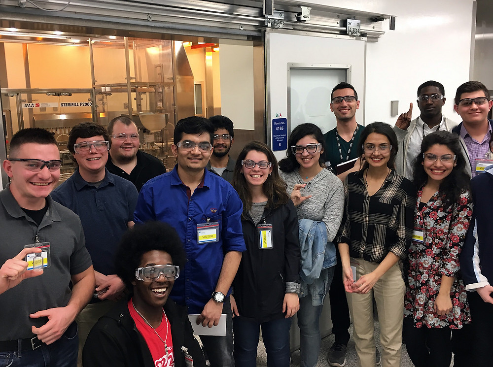 A group of people wearing safety goggles, standing inside Xellia Pharmaceuticals