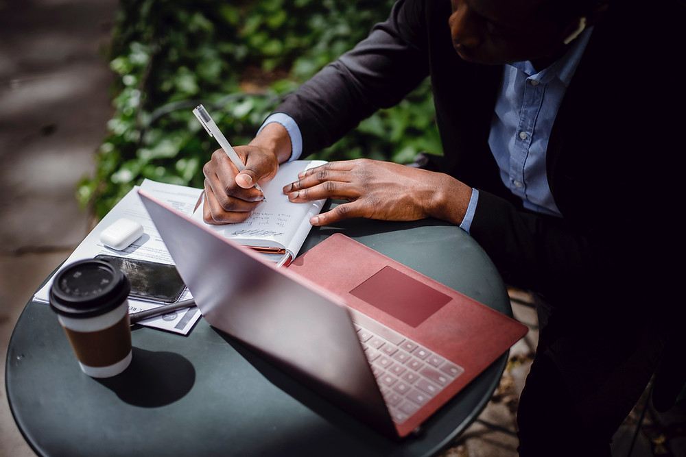 A man sits at a small café table outside. There is an open red laptop, a coffee cup, his phone, notebook, and papers on the table. He is dressed in a suit and writing on the notebook. There is greenery on the ground behind him.