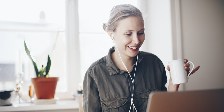 Women wearing headphones and drinking coffee while looking at her laptop