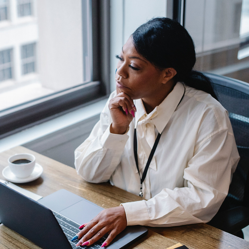 Woman sitting by an office window with a coffee cup and laptop in front of her. She has her hand on her chin and is looking outside contemplatively.