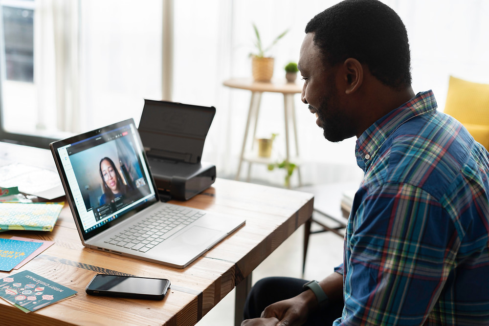 A man wearing a blue patterned shirt sitting at a wooden table with an open laptop in front of him. He is in a virtual meeting with a woman on the laptop screen.