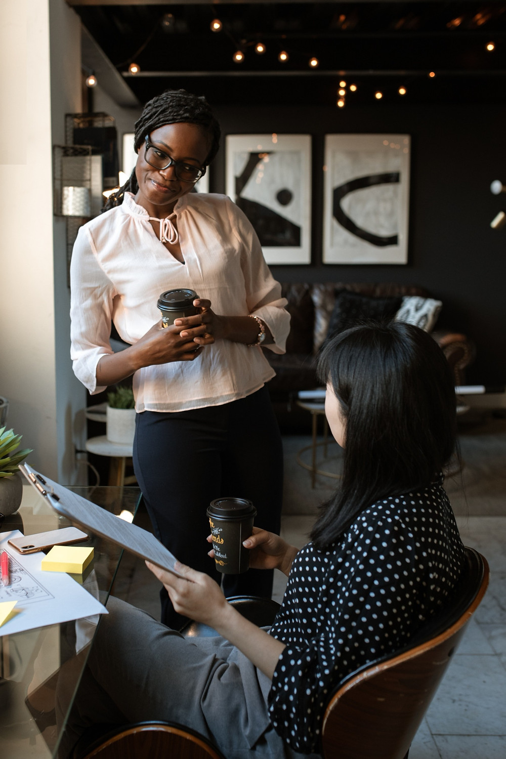 Two women talking in a coffee shop. The one facing the camera is smiling and wearing black frame glasses, a pink blouse and black slacks, holding a to-go coffee up, and standing. The second is seated with her back to the camera, is wearing a black with white polka-dot blouse, gray slacks, and holding a clipboard and to-go coffee cup.
