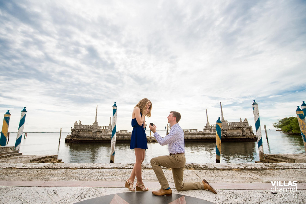 a man in his knees proposing to his long time blonde girlfriend wearing a blue dress in a beautiful background of bay area at Vizcaya Museum and Gardens