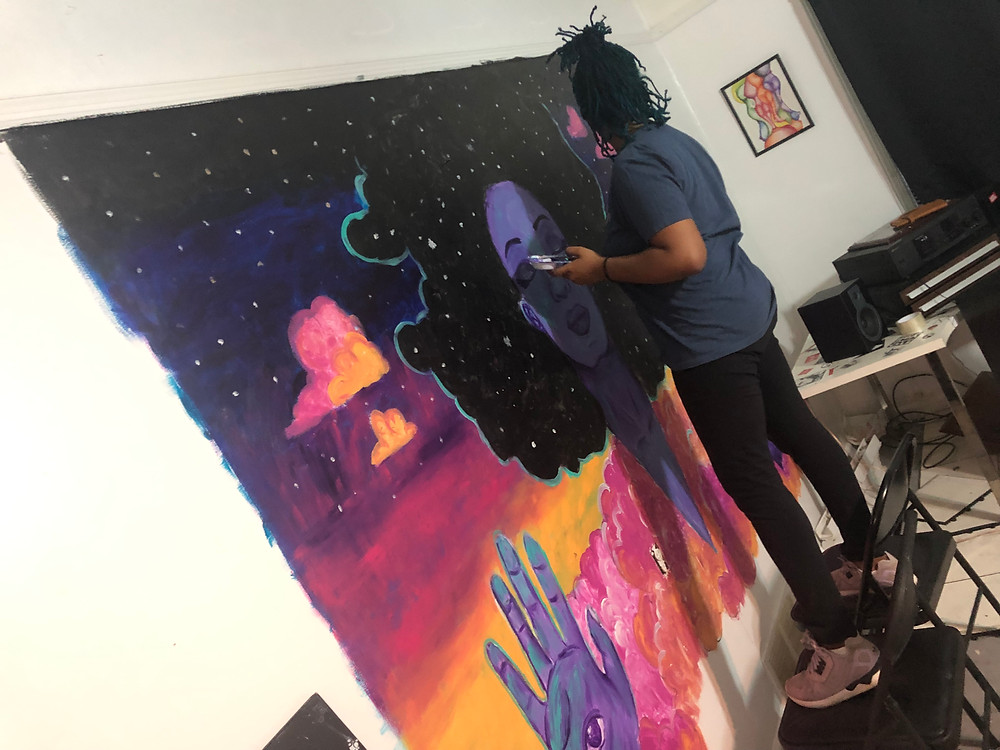 Black woman painting on wall.