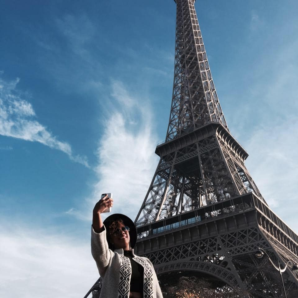black woman in front of eiffel tower in paris, france.