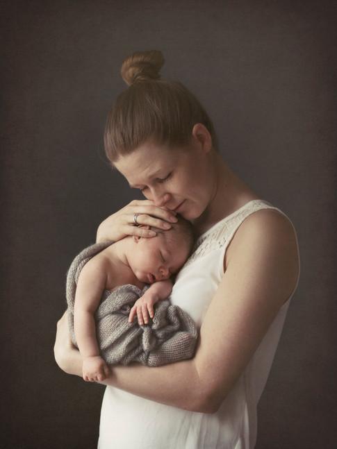 Nyfødt baby i mors armer.