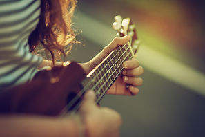 Young hipster girl  playing guitar ukule