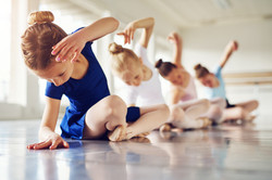 Little ballerinas doing exercises and bending sitting on floor in ballet class.