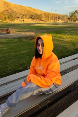 Model wearing Orange Love Yourself hoodie in size Medium