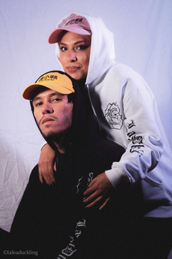 Models wearing pink and yellow Lafeaduckling dad hats with white and black Rose Lens hoodies