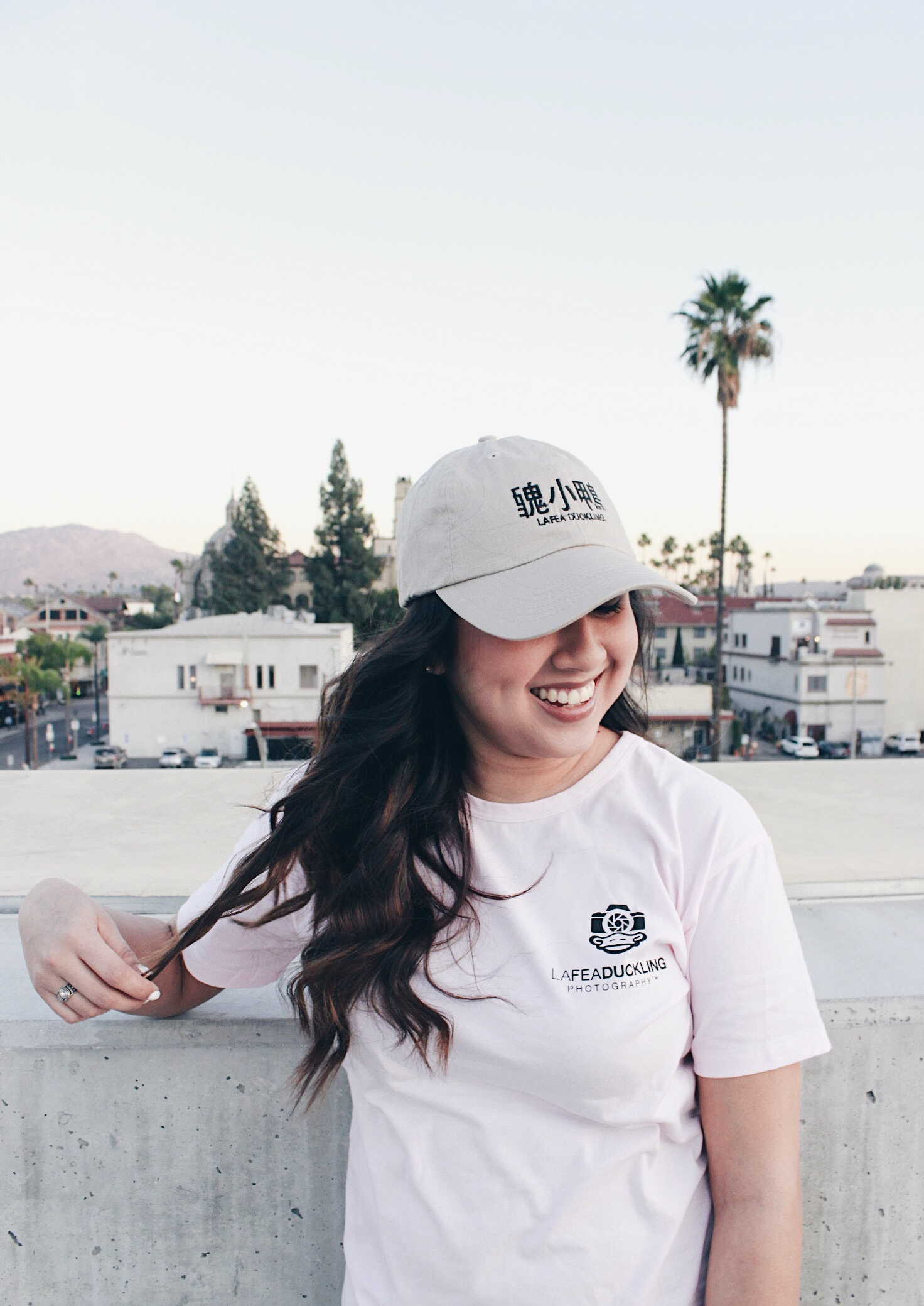 Model wearing grey Lafeaduckling dad hat with pink Lafeaduckling Photography tee